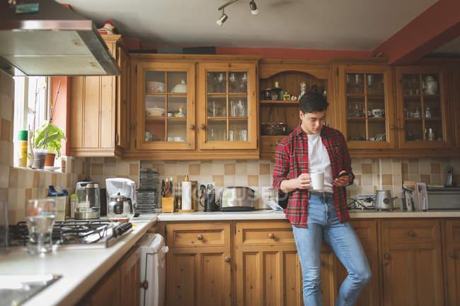 Людина за допомогою мобільного телефону та проведення чашку кави в кухні в домашніх умовах. — стокове фото