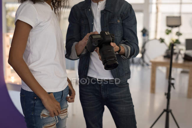 Mid section of photographer showing photos to fashion model on digital camera — Stock Photo