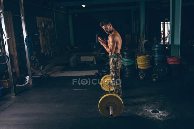 Мышечный человек трения порошок в руках во время тренировки с штангой — стоковое фото
