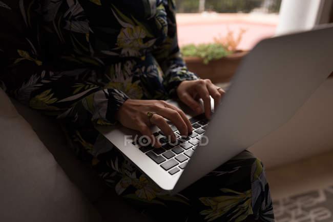 Sección media de la mujer musulmana usando el ordenador portátil en casa - foto de stock