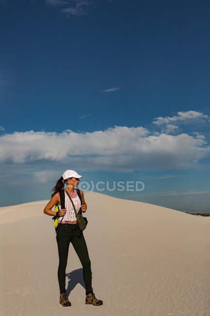 Randonneuse avec sac à dos debout sur le sable par une journée ensoleillée — Photo de stock