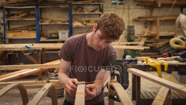 Young male carpenter working in workshop — Stock Photo