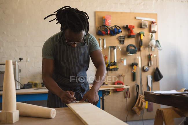 Carpenter measuring wooden plank in workshop — Stock Photo