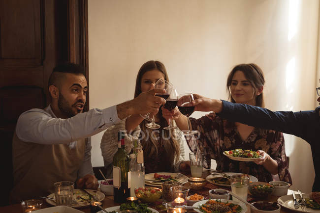Friends toasting wine while having meal at table — Stock Photo