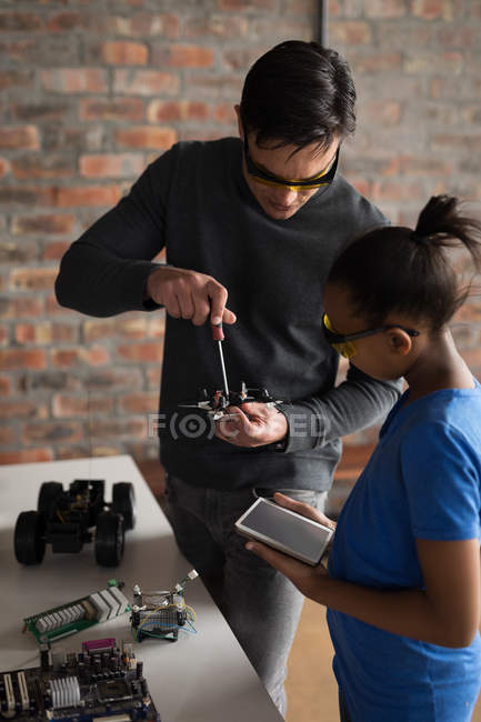 Father and daughter with tablet computer repairing drone in office. — Stock Photo