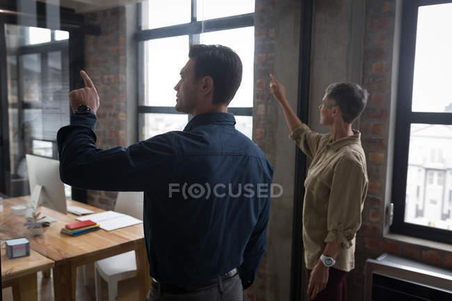 Collègues d'affaires utilisant écran invisible dans le bureau . — Photo de stock