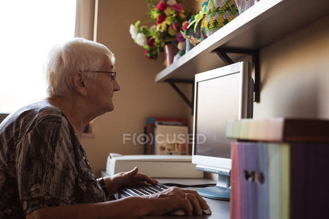 Femme âgée travaillant sur ordinateur à la maison de soins infirmiers — Photo de stock