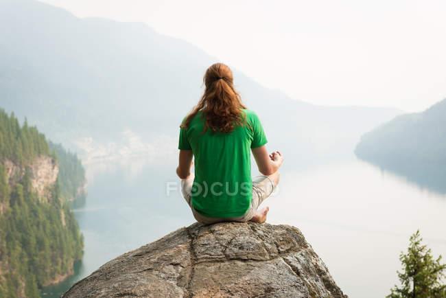 Прилежный человек, сидящий в позе медитирующего на краю скалы на рассвете — стоковое фото