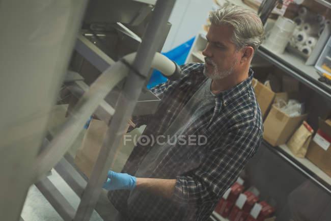 Man refining grain in machine at factory — Stock Photo