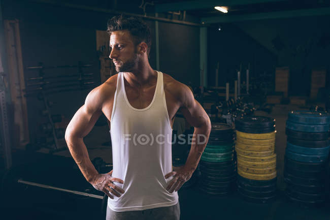 Determined muscular man standing with hands on hip in the fitness studio — Stock Photo