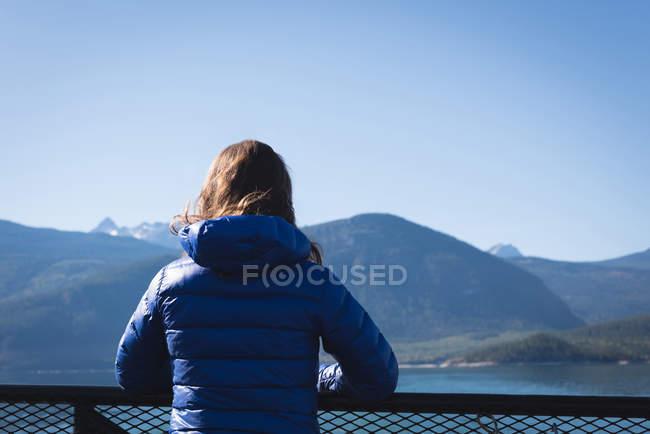 Vista trasera de la mujer mirando a la vista en un día soleado - foto de stock