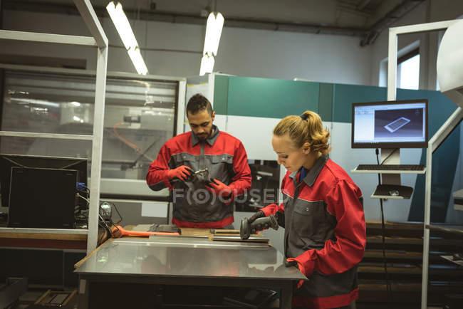 Dos trabajadores que operan una máquina de escaneo en fábrica - foto de stock