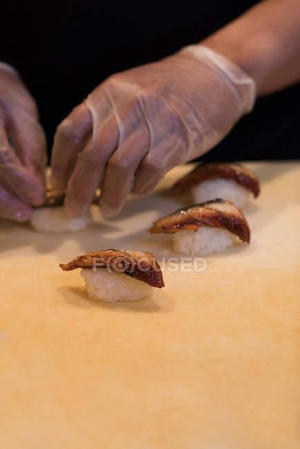 Chef preparando sushi em uma tábua de corte na cozinha — Fotografia de Stock