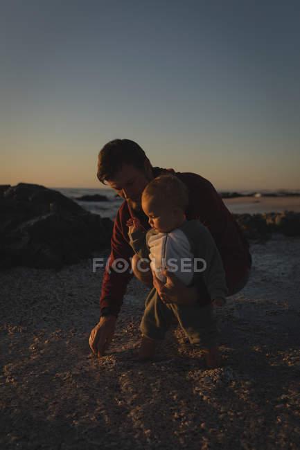 Padre e figlio giocano sulla sabbia in spiaggia durante il tramonto — Foto stock