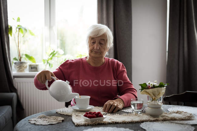 Senior woman pouring tea into cup from tea pot at home — Stock Photo
