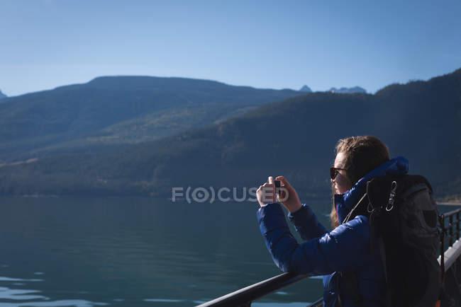 Belle femme prenant des photos avec téléphone mobile par une journée ensoleillée — Photo de stock