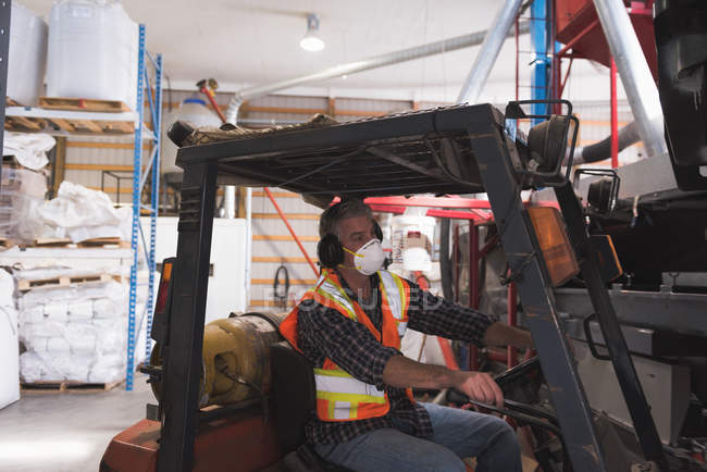 Man in protective workwear sitting in forklift at factory — Stock Photo