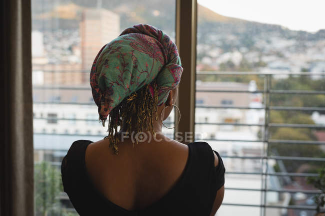 Rear view of woman in headscarf looking through window at home. — Stock Photo