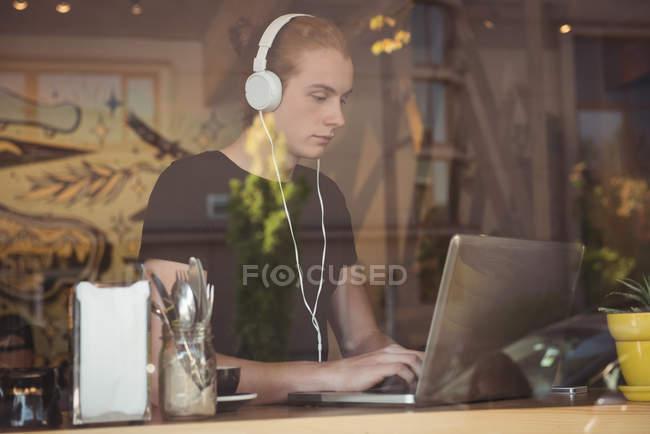 Mann hört Musik über Kopfhörer, während er Laptop im Café benutzt — Stockfoto