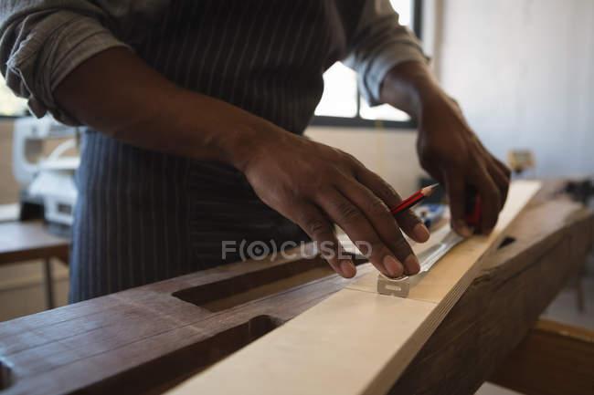 Mittelteil des Tischlers Messung der Holzplanke mit Waage in der Werkstatt — Stockfoto