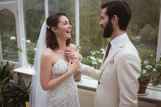 Marié heureux plaçant sa main sur la poitrine des mariées — Photo de stock