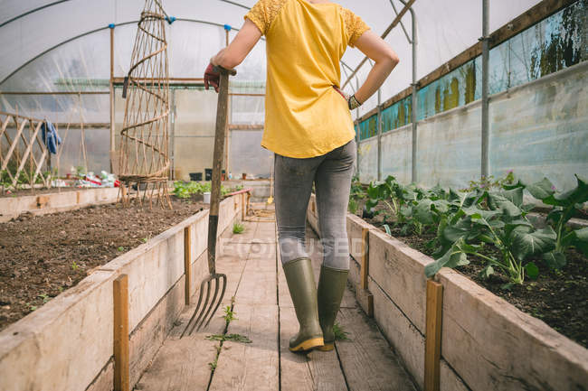 Low section of Woman with digging fork standing in greenhouse — Stock Photo