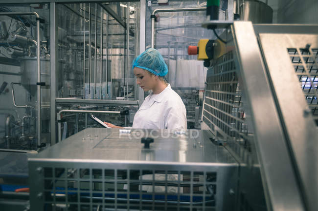 Female worker monitoring machine in the factory — Stock Photo