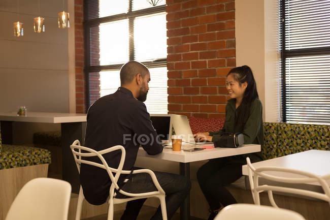 I colleghi d'affari che interagiscono con l'un l'altro in mensa a ufficio — Foto stock