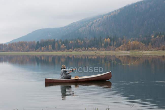 Homme et chien sur le bateau jetant la ligne de pêche au milieu de la rivière — Photo de stock