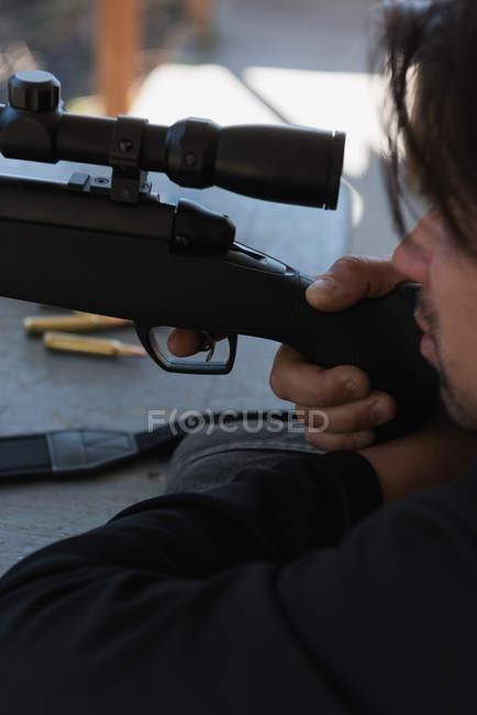 Человек, целящийся снайперской винтовкой в мишень в солнечный день — стоковое фото