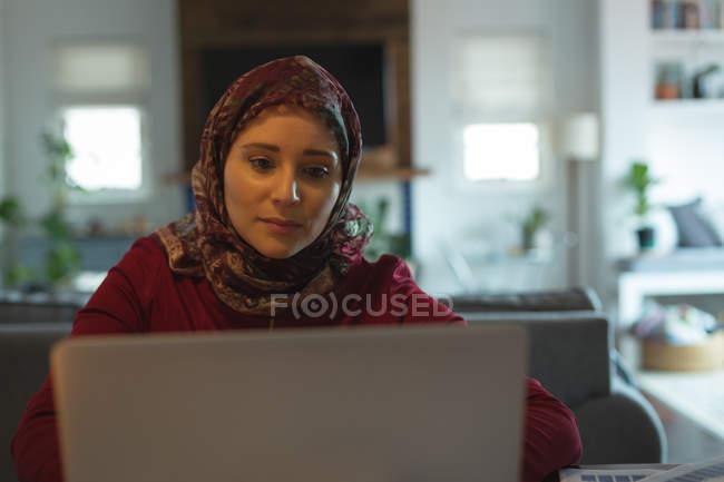 Mujer musulmana con el portátil en casa - foto de stock