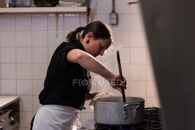 Chef stirring while cooking in the commercial kitchen — Stock Photo