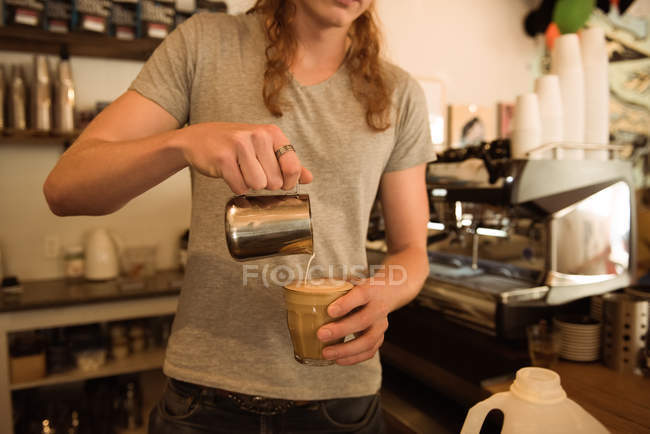 Mid section of barista making coffee at cafeteria counter — Stock Photo