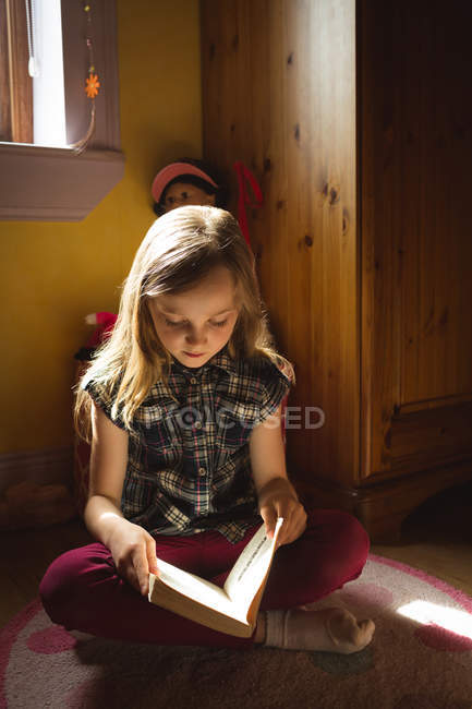 Young girl reading book in bedroom at home — Stock Photo
