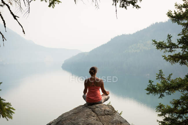 Fit woman sitting in meditating posture on the edge of a rock at the time of dawn — Stock Photo