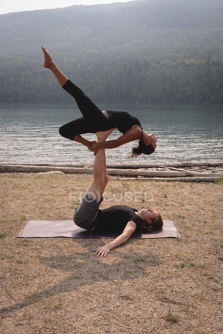 Подходящая пара практикует акро-йогу в пышной зеленой земле во время dawn — стоковое фото