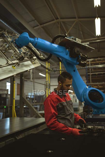 Trabajador masculino comprobando una pieza de la máquina en fábrica - foto de stock
