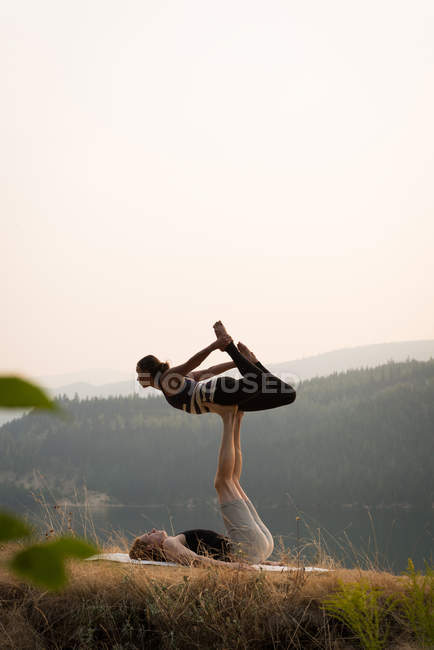 Sporty couple practicing acro yoga in a lush green ground at the time of dwan — Stock Photo