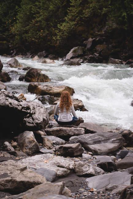 Rückansicht einer Frau, die auf Felsen in der Nähe eines fließenden Flusses sitzt — Stockfoto