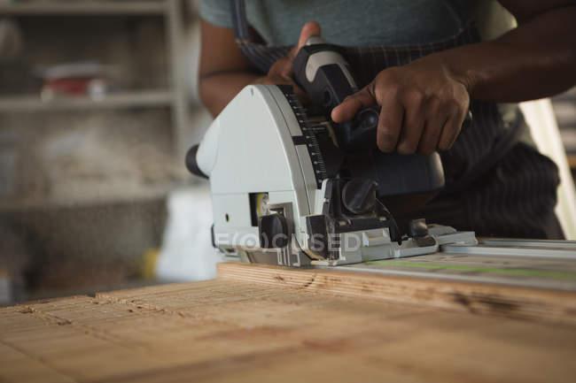 Середине раздел Карпентер, выравнивание древесины в мастерской — стоковое фото
