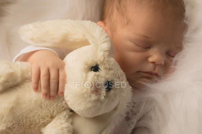 Новорожденный ребенок спит с кролика Плюшевая игрушка. — стоковое фото