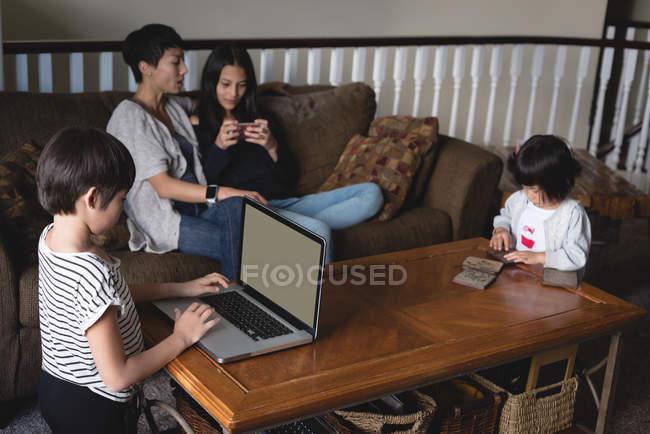 Хлопчик, використовуючи ноутбук під час мати і дочка, сидячи у фоновому режимі на дому — стокове фото