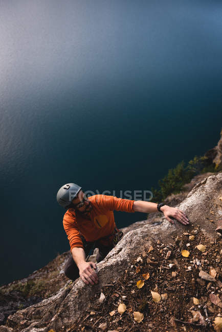 Rock climber reaching on the cliff top on a sunny day — Stock Photo