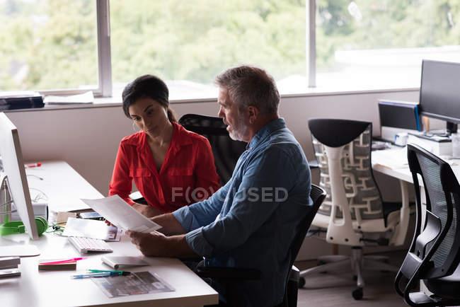 Колегами, обговорювати документи на столі в офісі творчої — стокове фото