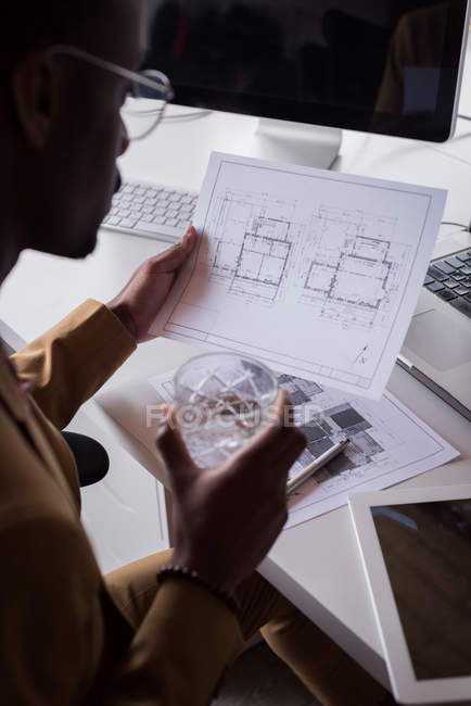 Close-up of male office executive checking blueprint on desk at creative office — Stock Photo