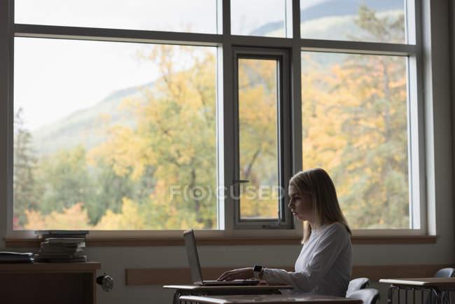 Teenage girl using laptop in classroom at university — Stock Photo