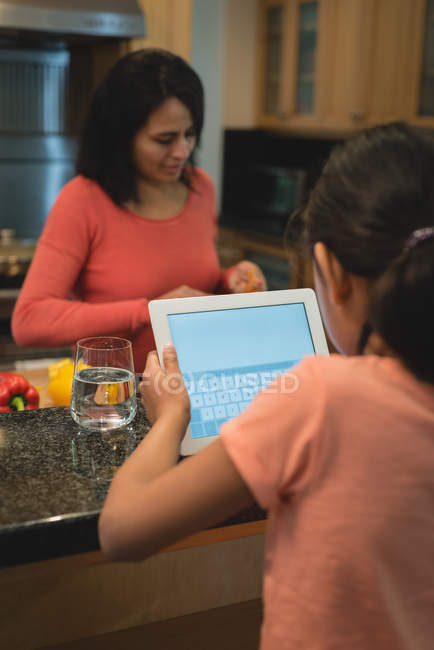 Girl using digital tablet while mother preparing food in kitchen at home — Stock Photo