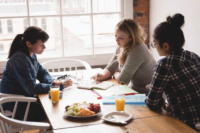 Female executives discussing with each other in the creative office — Stock Photo