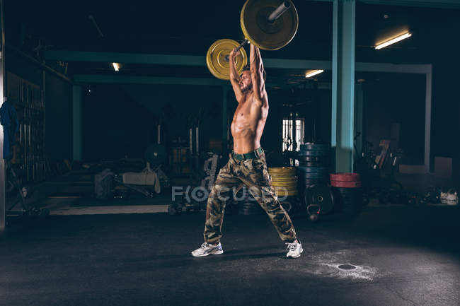 Muscular man exercising with barbell in the fitness studio — Stock Photo