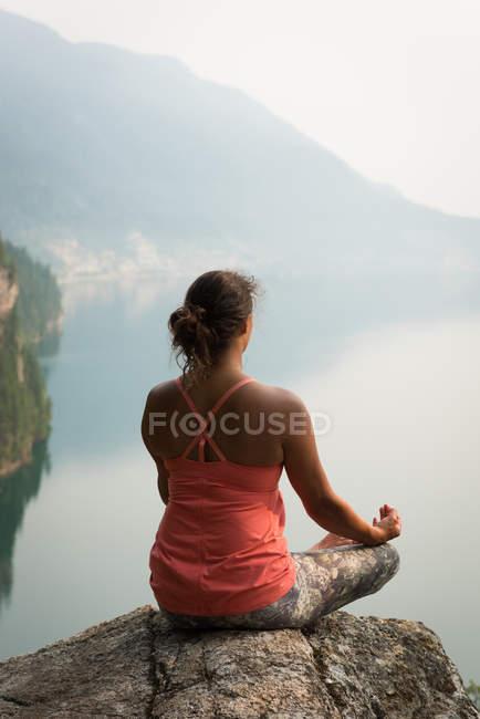Donna in forma seduta a meditare postura sul bordo di una roccia al momento dell'alba — Foto stock
